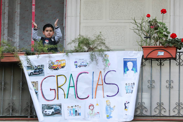 Criança bate palmas na varanda de sua casa em Barcelona em homenagem aos profissionais de saúde