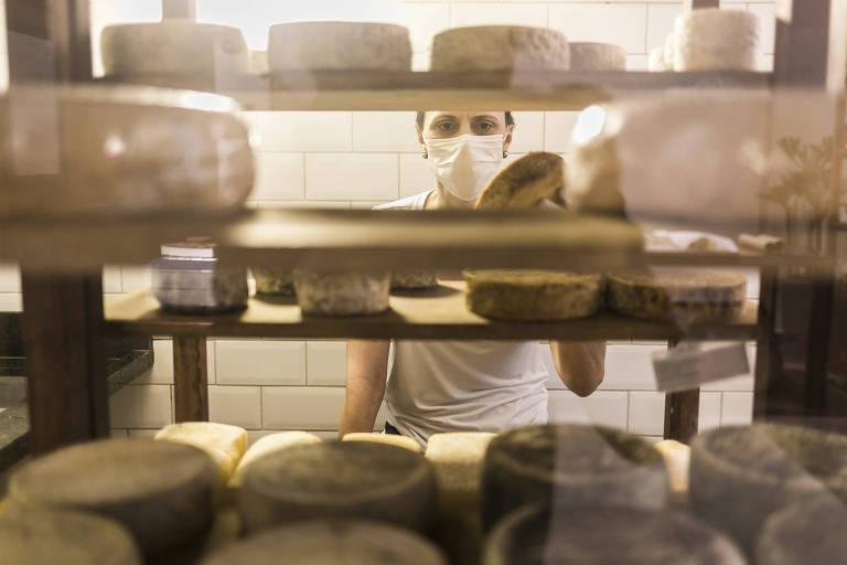 Letícia Vilas Boas coloca os queijos em prateleiras de madeiras usando uma máscara de proteção
