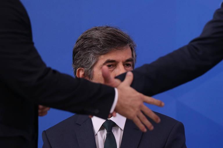 Observados pelo novo ministro da Saúde, Nelson Teich, o presidente Jair Bolsonaro cumprimenta o procurador-geral da República, Augusto Aras. Os braços do presidente e do procurador-geral se cruzam em frente ao rosto de Teich