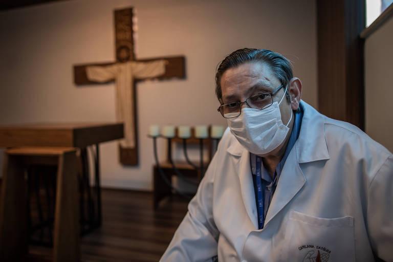 O padre João Inacio Mildner, capelão do Emílio Ribas, de jaleco e máscara, na capela do hospital, com cruz ao fundo