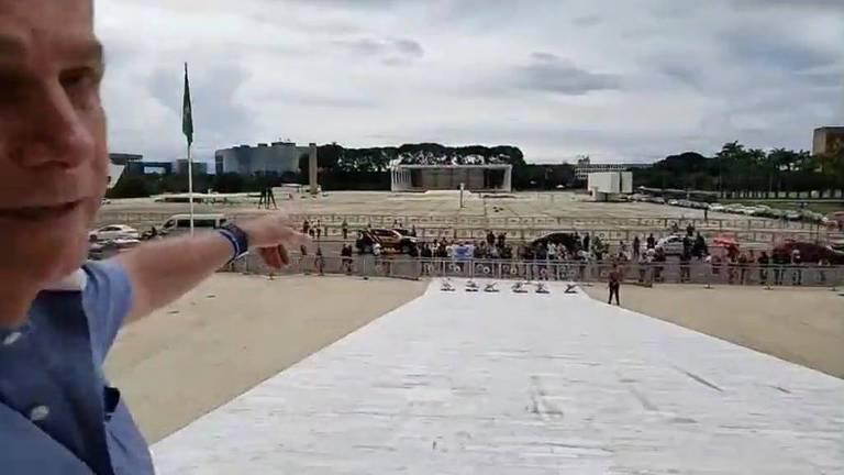 O presidente Jair Bolsonaro aponta para o STF em vídeo gravado no alto da rampa do Planalto, em Brasília, ao comentar decisão da corte de que estados e municípios têm autonomia para determinar o isolamento social em meio à pandemia do coronavírus