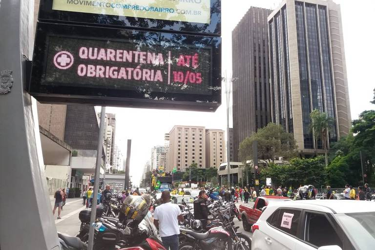 Foto mostra manifestantes contra Doria e a favor de Bolsonaro passando por painel com aviso sobre isolamento social em São Paulo