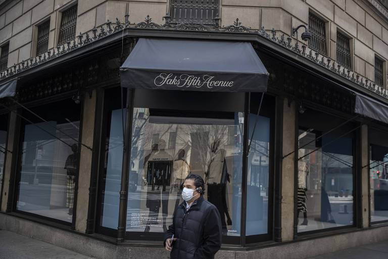 Pedestre passa pela loja de departamentos Saks, em Nova York, fechada por causa do isolamento provocado pela pandemia