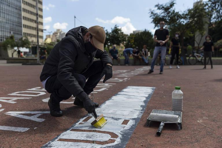 Imagem mostra Victor Ghiraldini, 42, produtor gráfico do Estúdio Miolo, que teve a ideia de pintar frases motivacionais seguidas pela #fiqueemcasa, durante ação na praça Roosevelt; ao todo, 25 pontos da cidade vão receber as intervenções artísticas, que têm apoio da Prefeitura de São Paulo