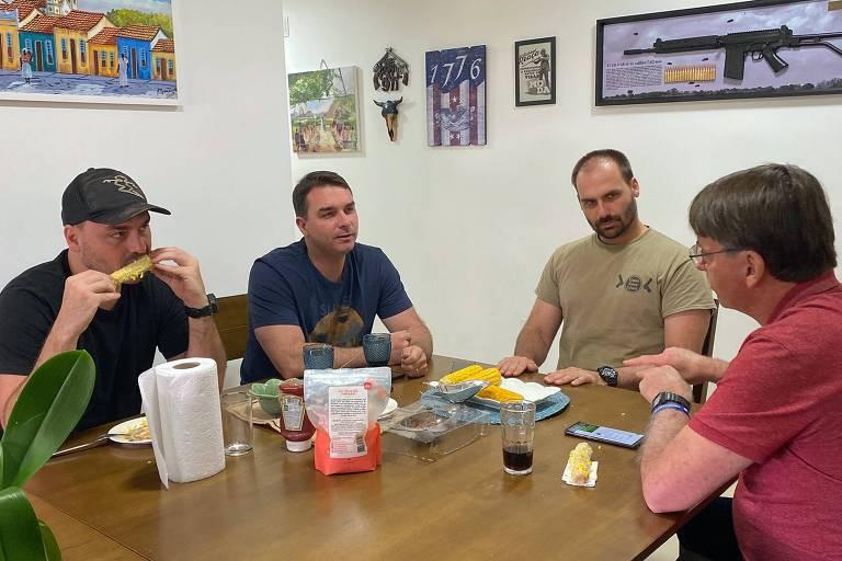Eduardo Bolsonaro sentado à mesa com o pai Jair Bolsonaro e seus irmão Flávio e Carlos (com uma espiga de milho na boca)