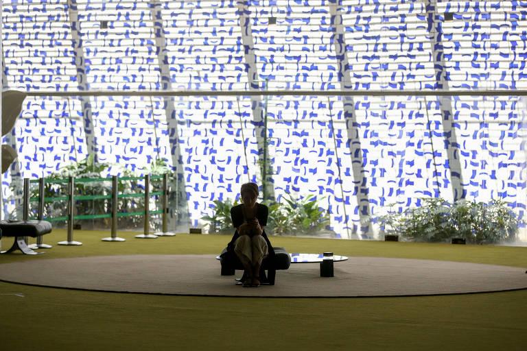Mulher sentada sozinha em espaço amplo, com iluminação em mural ao fundo