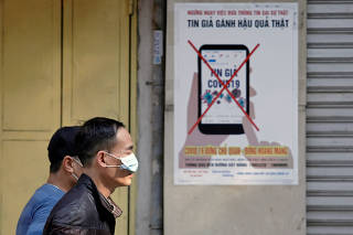 Men wear protective masks as they walk past a poster warning against the spread of 'fake news' online on the new coronavirus in Hanoi