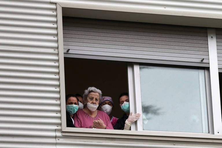 Idosa e enfermeiras olham pela janela de uma casa de idosos em Barcelona, na Espanha, durante pandemia do novo coronavírus no país