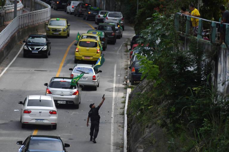 Policial aponta arma em direção a moradores da comunidade do Vidigal, no Rio, contrários a protesto pró-Bolsonaro, neste domingo (20)