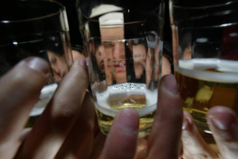 O abuso de bebidas alcoólicas durante a quarentena pode causar efeitos psíquicos, além de alterar o sistema imune; na foto vemos três copos de bar, com cerveja, em primeiro plano; ao fundo, distorcidos pelos copos, entrevemos os rostos de quem os segura