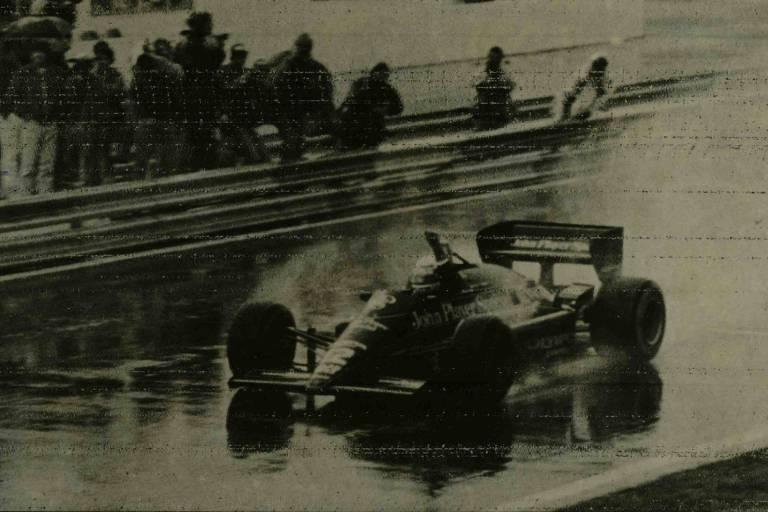 Senna ergue o braço dentro do carro em pista encharcada