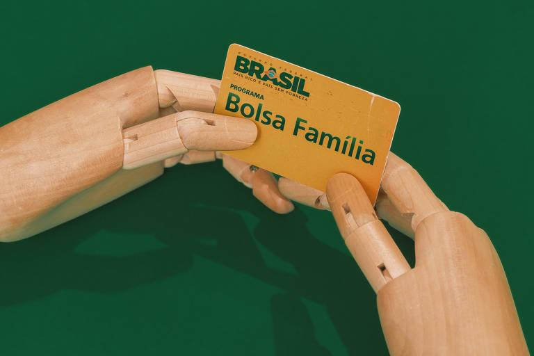 Foto mostra um fundo verde com duas mãos articuladas segurando um cartão amarelo do Bolsa Família.