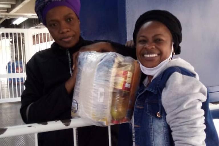 Congolesa Sylvie Mutiene (à dir.) distribui cesta básica a outra imigrante