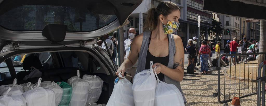 A produtora Mariana Calvo, 35, descarrega marmitas na tenda montada pelos franciscanos no Largo São Francisco