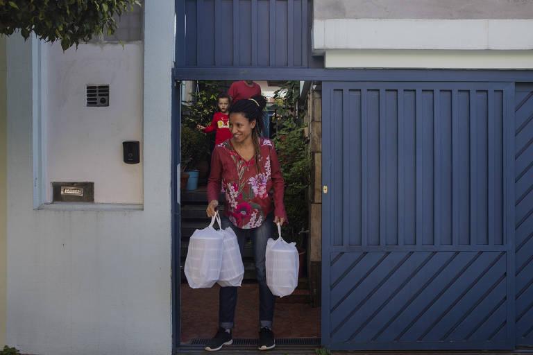 Voluntária aguarda para entregar refeições que cozinhou