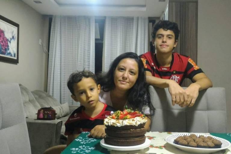 Danyelle Santos comemora seu aniversário em isolamento com os filhos; vemos a mãe sentada à mesa, com o filho menor no colo, enquanto o maior, adolescente, está de pé atrás da cadeira dela; na mesa, um bolo de chocolate com creme e morangos e um prato de brigadeiros