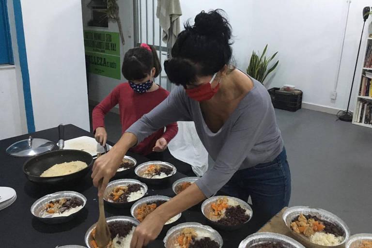Consuelo Bassanesi e sua filha, Agnes, preparam, em casa, marmitas para o coletivo Mais Amor Menos Capital, no Rio; vemos mãe e filha, usando máscaras de tecido, preenchendo com comida caseira uma série de quentinhas sobre uma mesa