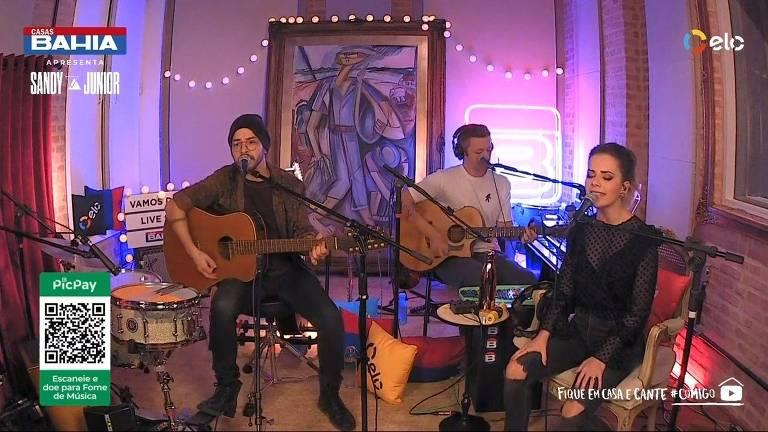 três pessoas em um cômodo cantando e tocando instrumentos