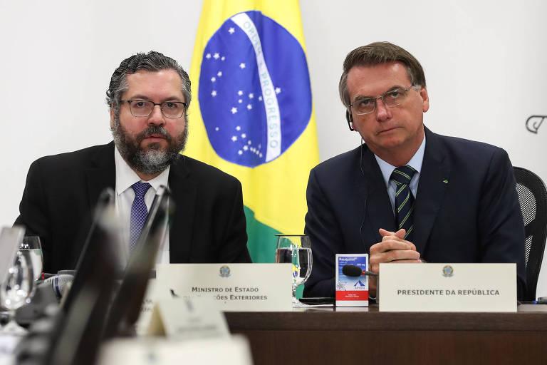 O chanceler Ernesto Araújo, à esq., e o presidente Jair Bolsonaro durante reunião do G20, por teleconferência, em Brasília