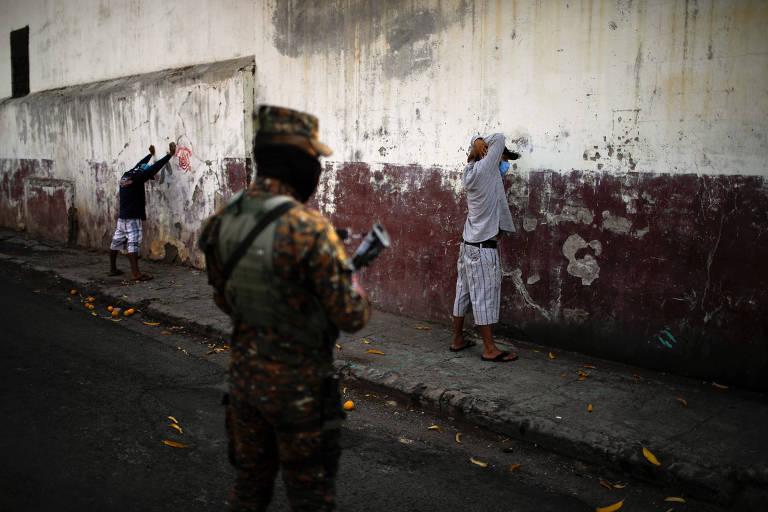 Militares salvadorenhos detêm homens durante operação para impor quarentena na cidade de La Libertad, a 30km de San Salvador
