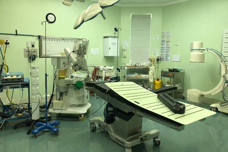 Sala de hospital com paredes verde claro, uma maca e diversos equipamentos hospitalares. Não há pessoas