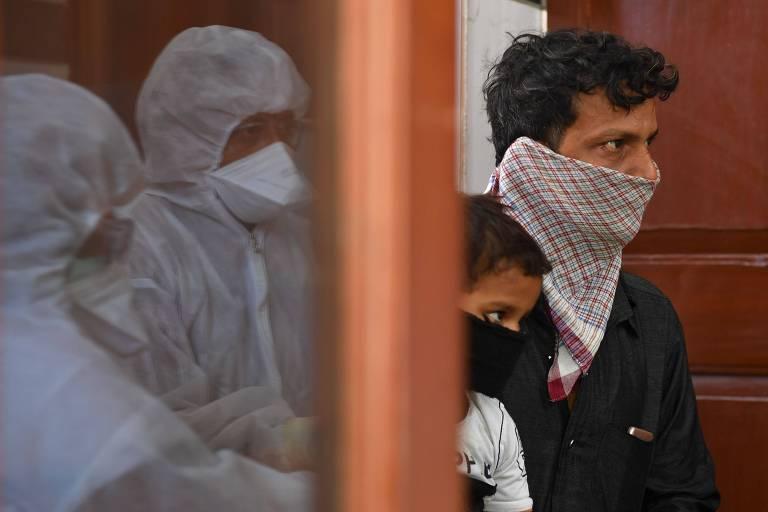 Observados por médicos, pai e filho entram em posto de saúde para serem testados para coronavírus em Mumbai, na Índia