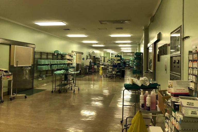 uma sala grande, onde estão guardados produtos e roupas hospitalares. A luz não é muito forte, não há pessoas, as paredes são verdes