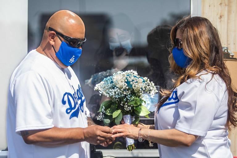 Philip Hernandez, à esquerda, coloca aliança na mão de sua noiva, Marcela Peru, enquanto a escrivã Erika Patronas observa casal em cerimônia em Anaheim, na Califórnia