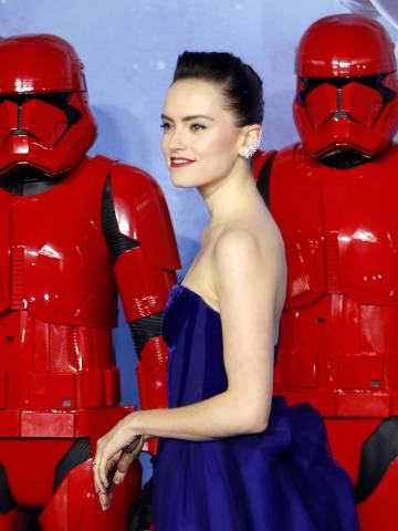 (FILES) In this file photo taken on December 18, 2019 British actor Daisy Ridley poses with sith stormtroopers on the red carpet upon arrival for the European film premiere of Star Wars: The Rise of Skywalker in London. -