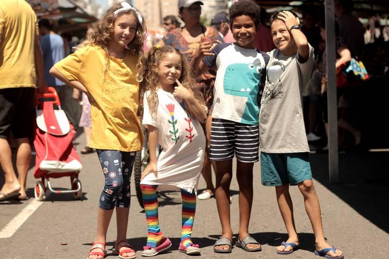 Duas meninas e dois meninos, de bermuda e chinelo e camisetas largas, abraçados olhando para a câmera