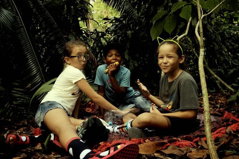 Duas meninas e um menino, no meio da mata, fazendo um piquenique