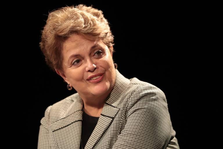 Em fundo preto está Dilma, de paletó cinza com estampa gráfica e blusa preta por baixo. Ela aparece do colo para cima