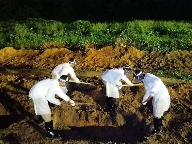 Funcionários com equipamento de proteção abrem cova no Cemitério Parque das Flores, no Recife