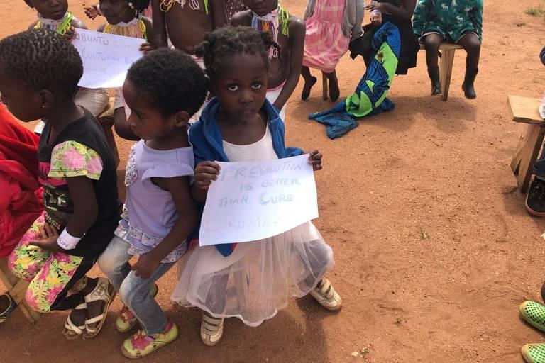 """Criança refugiada no Maláui segura papel com os dizeres: """"Prevenção é melhor do que a cura"""""""