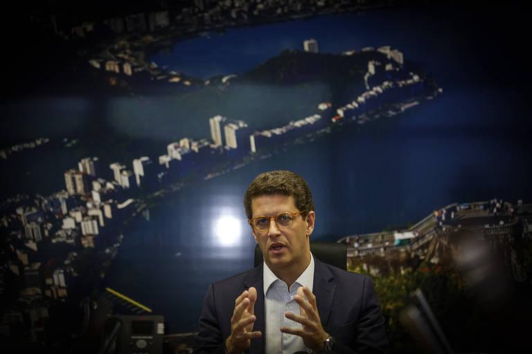 O ministro do Meio Ambiente, Ricardo Salles, movimenta as mãos em frente a um grande quadro