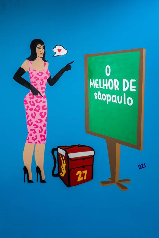 """Grafite em parede azul mostra mulher de vestido com estampa de onça nas cores rosa e pink, apontando para lousa onde se lê """"O Melhor de sãopaulo"""""""