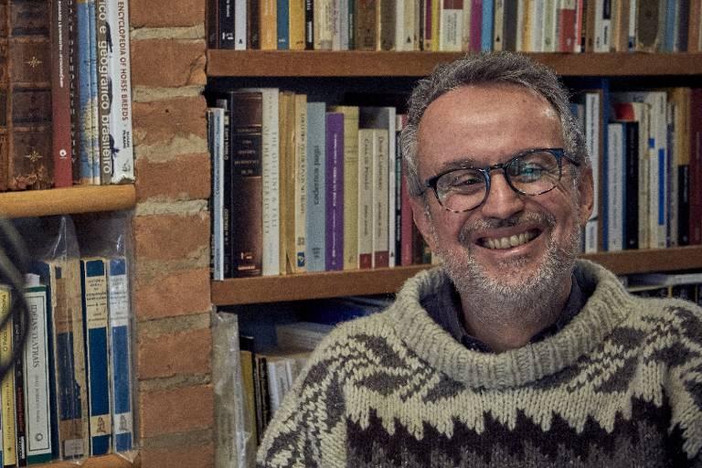 Homem sorrindo com estante de livros ao fundo