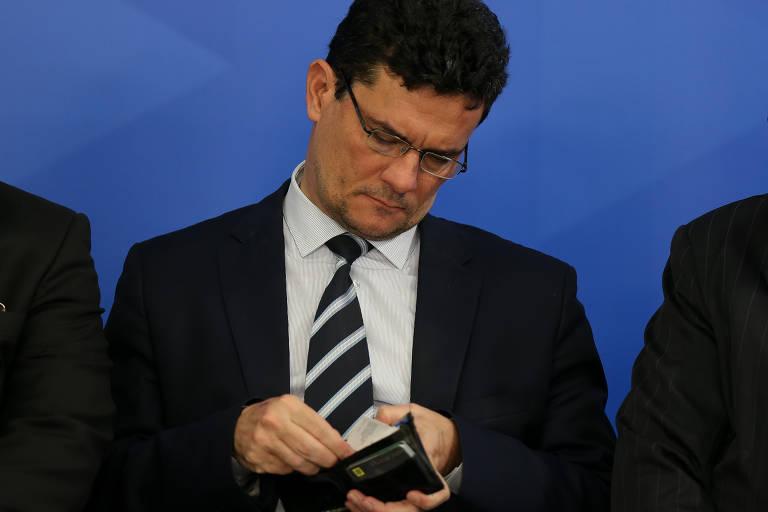 Sergio Moro, de óculos, analisa o conteúdo de uma carteira aberta em suas mãos