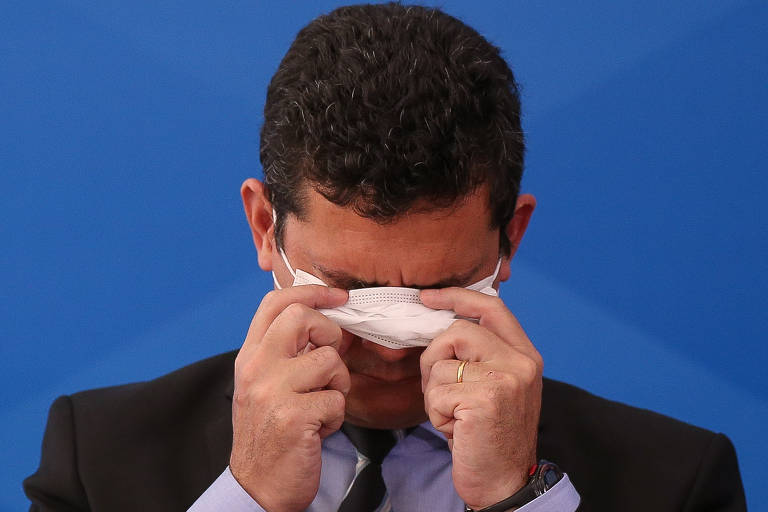 Sergio Moro usa as duas mãos para colocar máscara cirúrgica no rosto