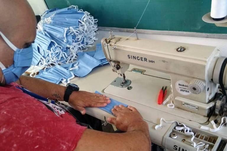 Voluntário confecciona máscara em máquina de costura
