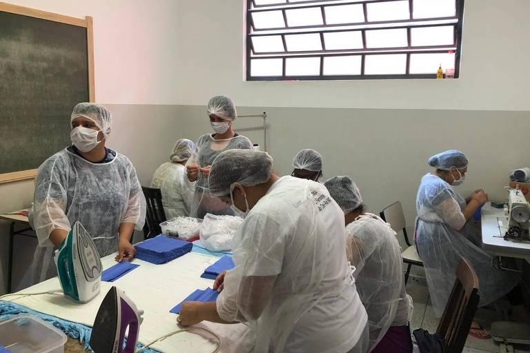 Mulher com trajes hospitales trabalham confeccionando máscaras cirúrgicas