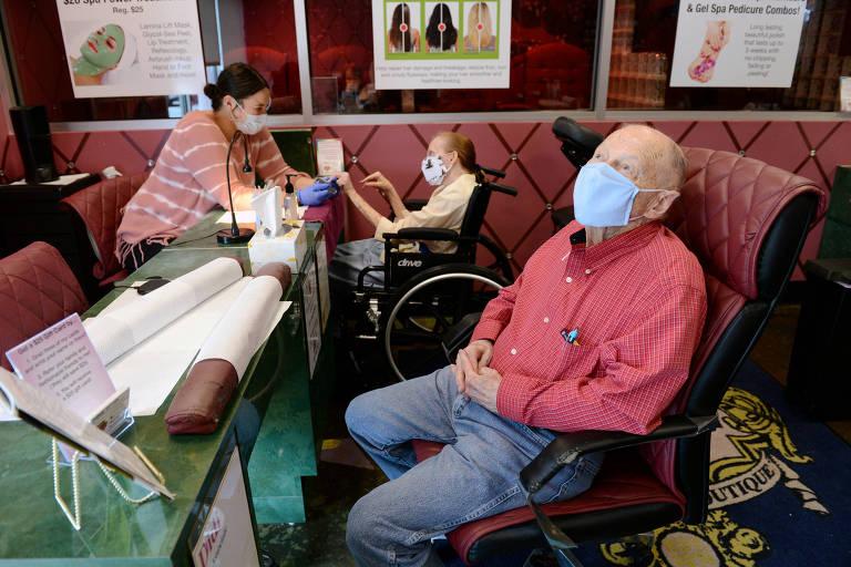 Homem espera sua mulher fazer as unhas em um salão de beleza em Marietta, na Geórgia, nos EUA