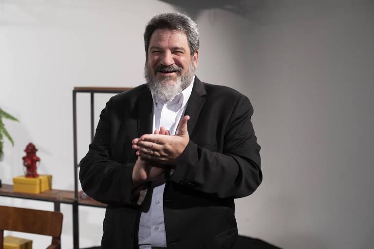 O filósofo, educador e escritor Mario Sergio Cortella é um homem corpulento e sorridente, com cabelos e barba grisalhos; na foto, usa camisa branca e blazer escuro, e faz um gesto semelhante ao de aplaudir