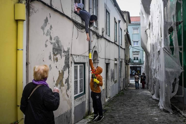 Homem dá um cravo a moradora de Benfica