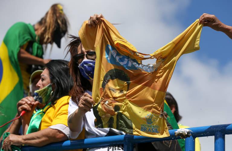 Manifestantes seguram uma camiseta em tom amarelo, com o rosto de Moro; a roupa tem um buraco, feito pelo fogo