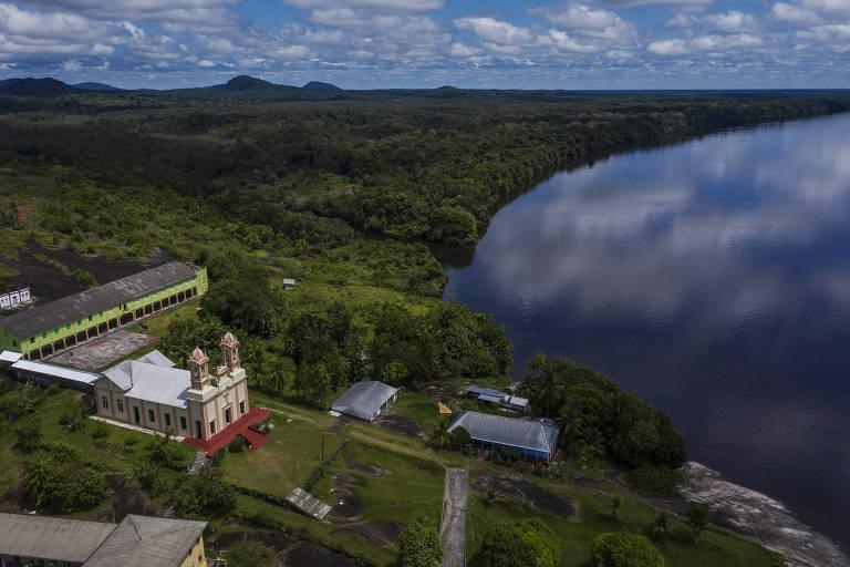 Vista aérea de igreja às margens de um rio em meio a floresta que se estende por toda a paisagem