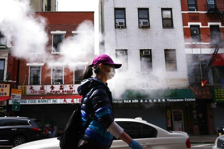 Mulher anda com máscara em Chinatown, área de concentração de imigrantes em Nova York