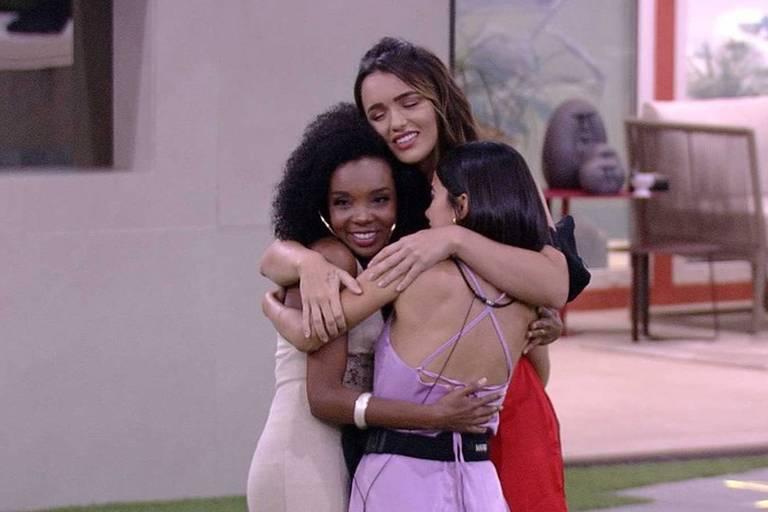 3 mulheres se abraçam no jardim