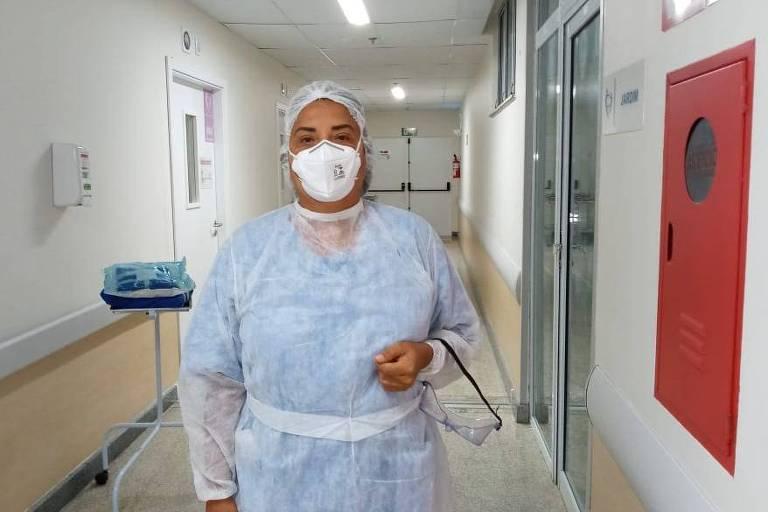 A enfermeira baiana Ana Cássia Tupiniquim, que foi alvo de fake news; vemos a profissional num corredor de hospital, usando avental descartável sobre o uniforme, máscara e touca no cabelo; no braço esquerdo, ela carrega o óculos de proteção que serve para evitar de tocar os olhos