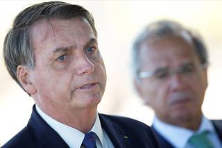 Brazil's President Jair Bolsonaro speaks near Brazil's Economy Minister Paulo Guedes while leaving Alvorada Palace in Brasilia